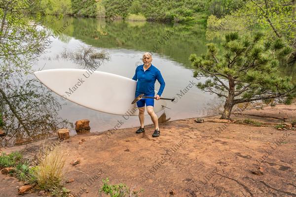 senior paddler with SUP paddleboard