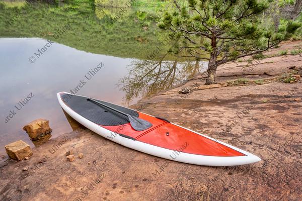stand up paddleborad on a rocky lake shore