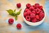 fresh red raspberries with green leaf