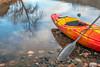 kayak with paddle on lake shore