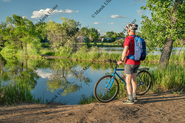 male cyclist with a mountain bike on a lake shore, summer scenery in Colorado