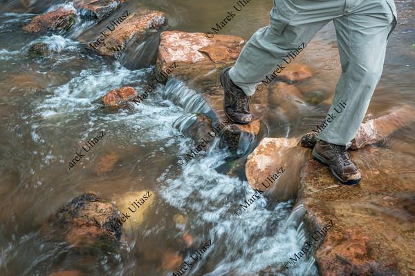 hiker crossing mountain creek