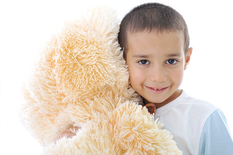 Portrait of a little kid hugging his teddy bear toy isolated in white