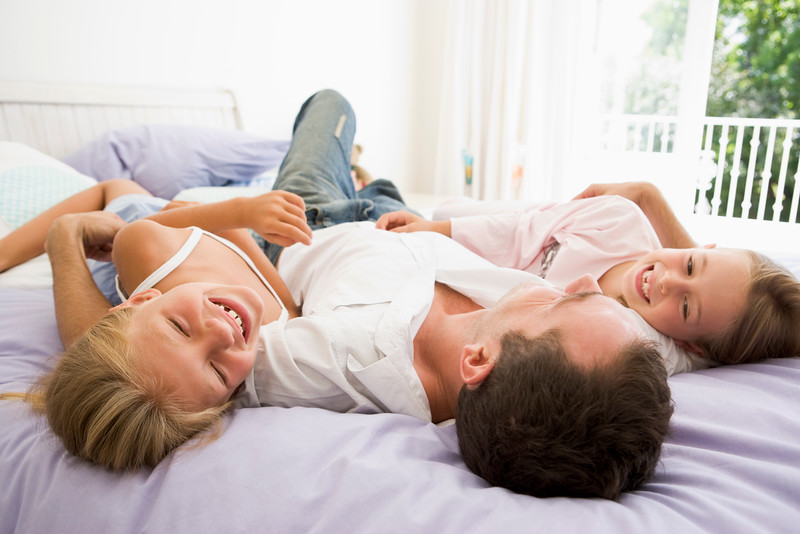 Man lying in bed with two young girls smiling