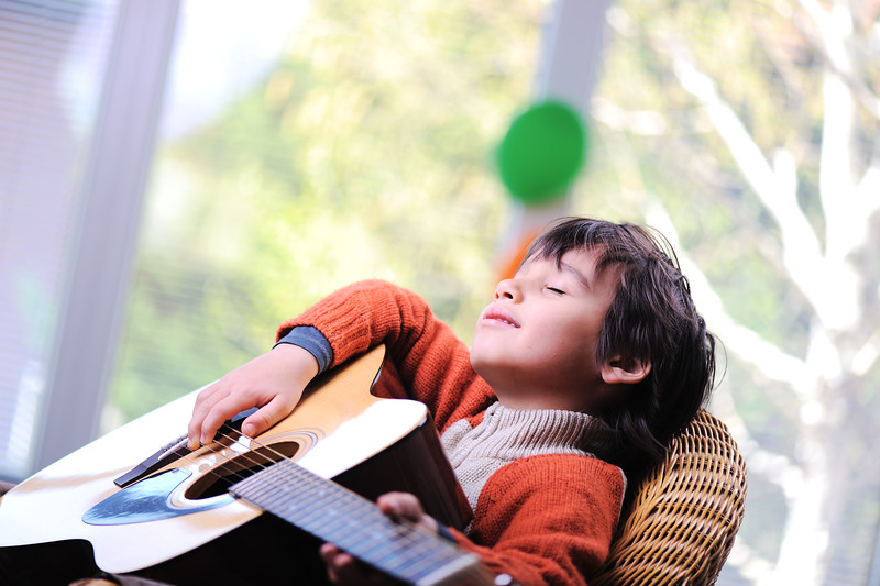 Kid playing guitar at home
