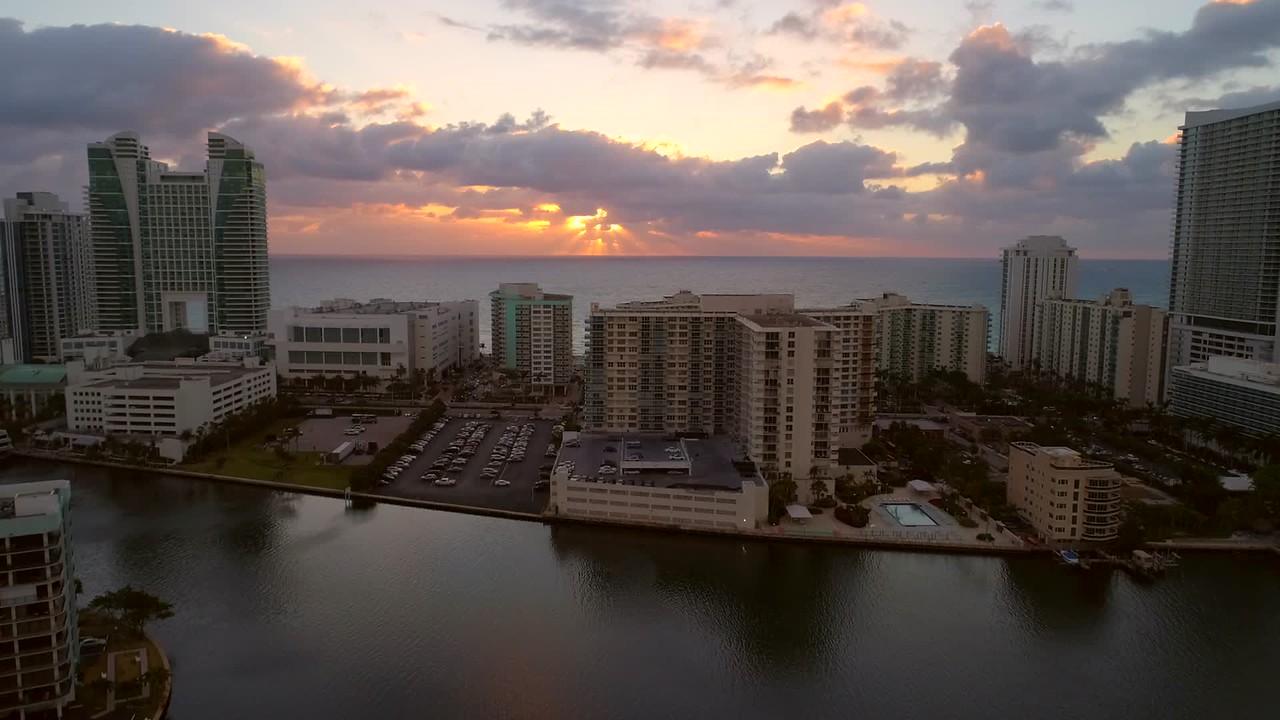Aerial drone passing apartment buildings reveal ocean sunrise 4k 60p