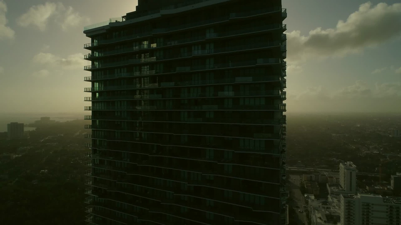 Aerial drone footage rising over dark eerie building sunset in backgound