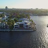 Aerial drone orbit shot of a luxury waterfront mansion under construction