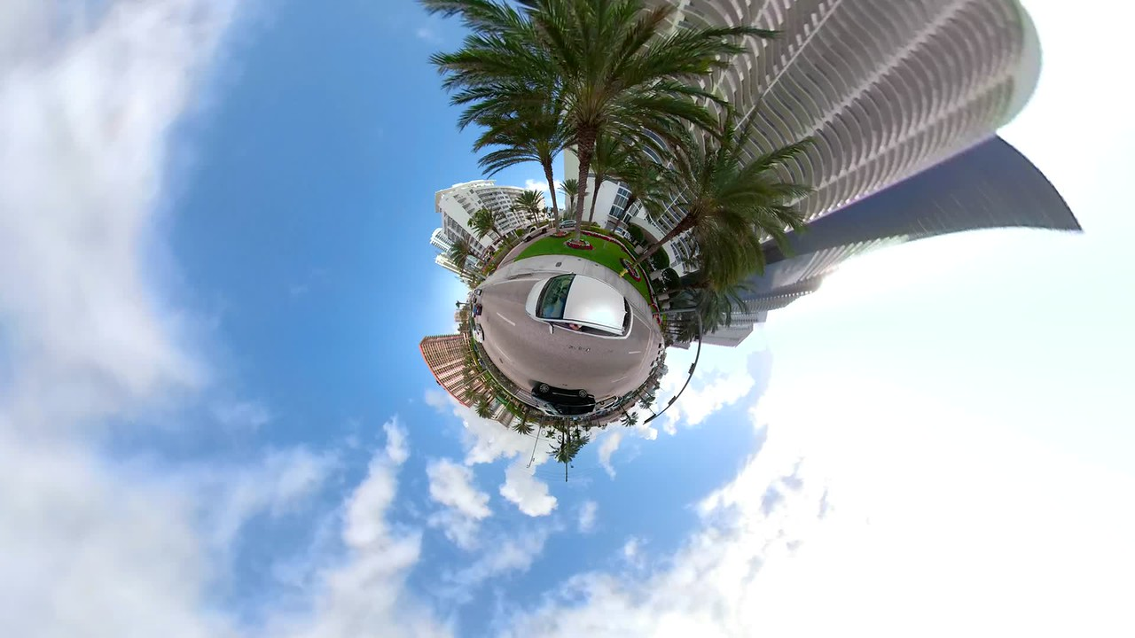 Car driving in a miniaturee tiny city planet with tall buildings