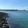 Calm waves crashing on shore rocks low aerial drone video