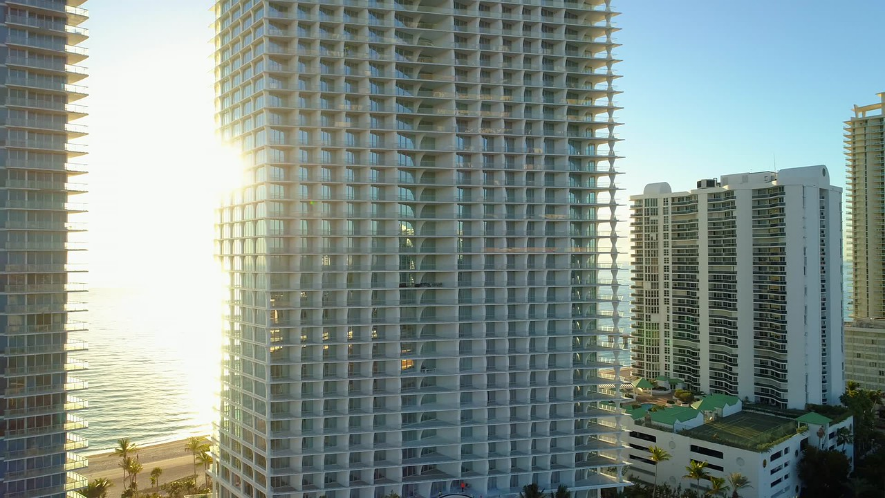 Bright morning sun and Florida condominiums on the ocean 4k 24p