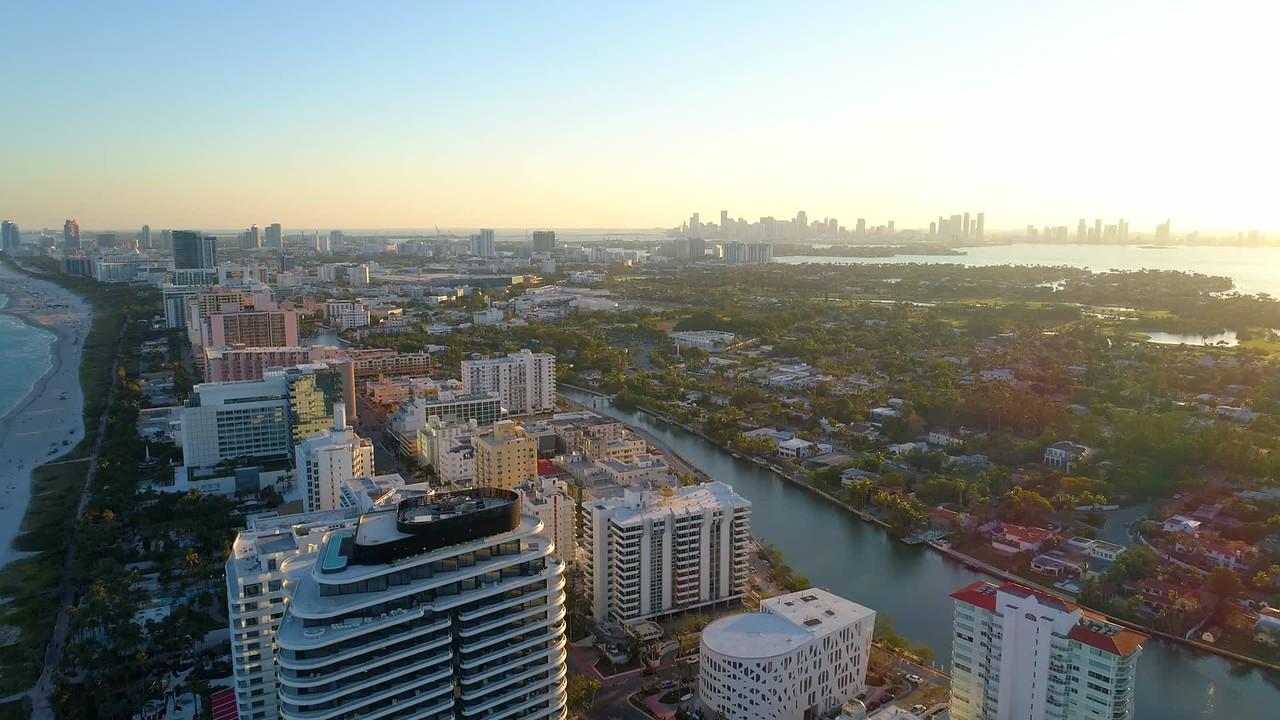 Aerial drone flight over Miami Beach condominiums on the beach sunset indian creek