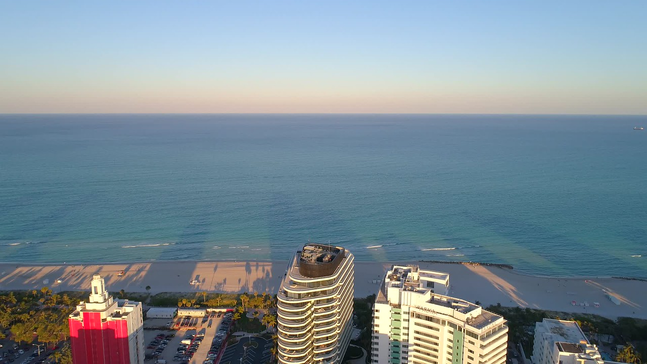 Aerial Miami Beach pull out shot showing condos on the beach