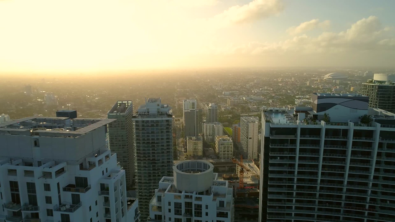 Aerial drone footage Brickell city skyscraper rooftops and backlit sunset