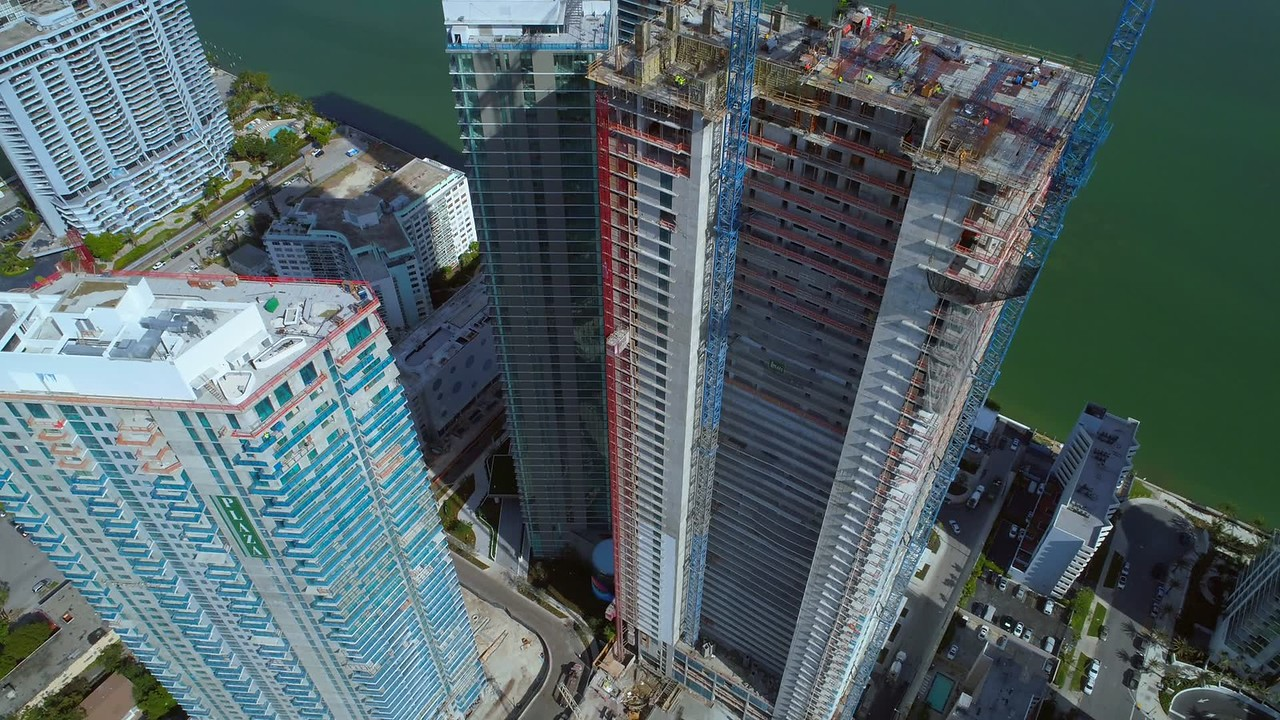 Aerial pull out reveal highrise buildings city construction with cranes 4k