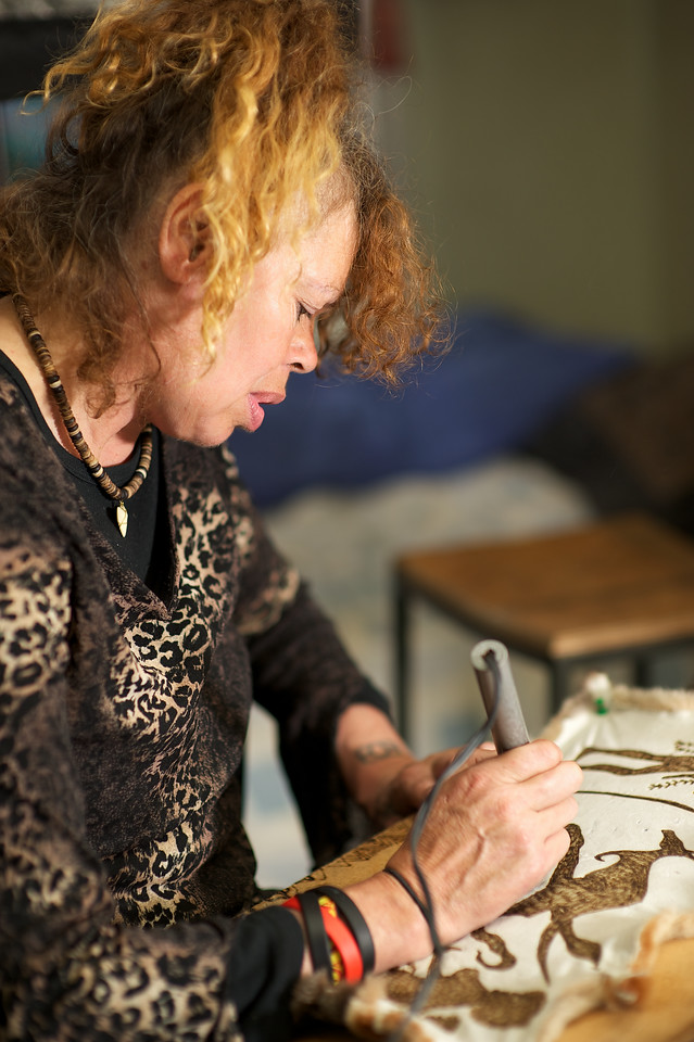 Female Indigenous Australian artist using a hot iron to burn a design into a possum skin