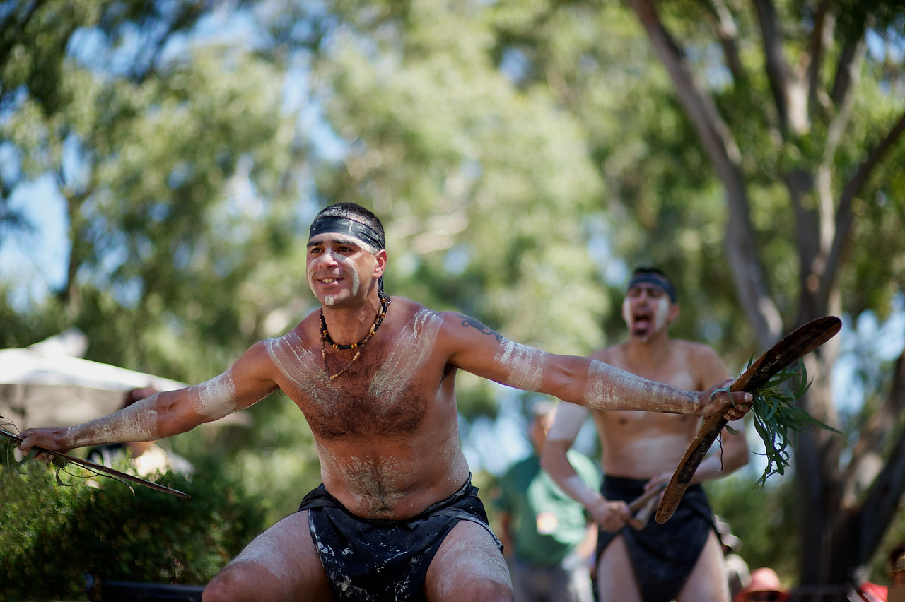 Two Aboriginal Dancers at an outdoor performance with a blurred green and blue background