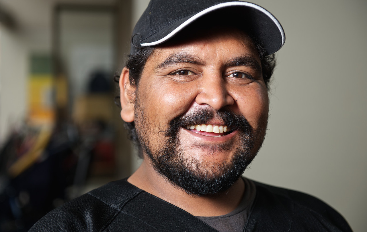 Twenty-five-year-od Indigenous Australian man smiling and on a blurred background.