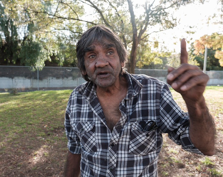 Aboriginal Man in Backyard Pointing Upwards