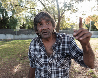 Aboriginal Man in Backyard Pointing Upwards