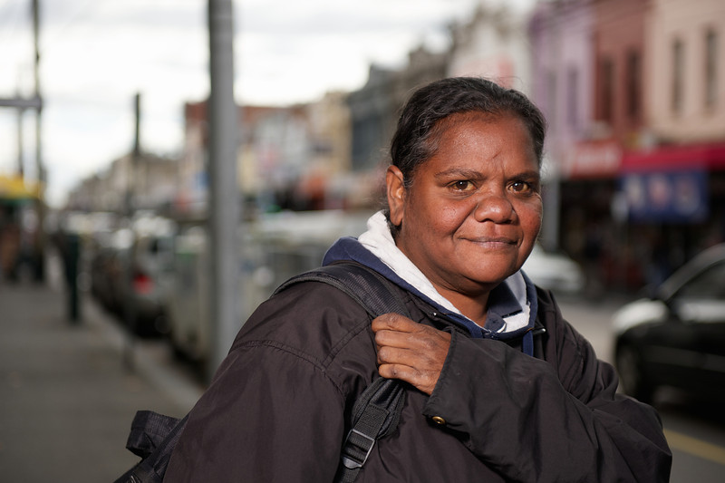 Aboriginal Woman on a shopping strip looking at camera, and on a blurred background.