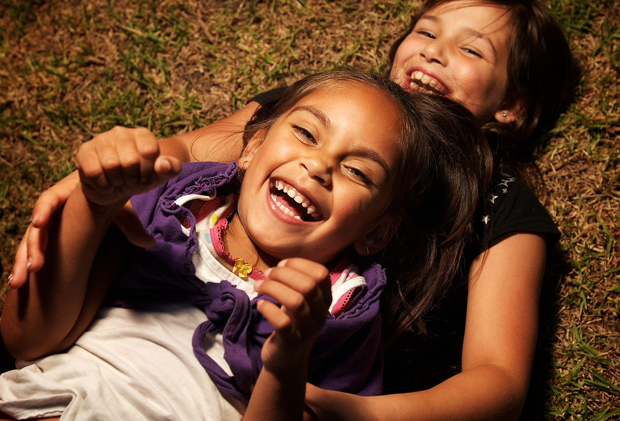 Aboriginal Girl laughing with Caucasian Girl on grass