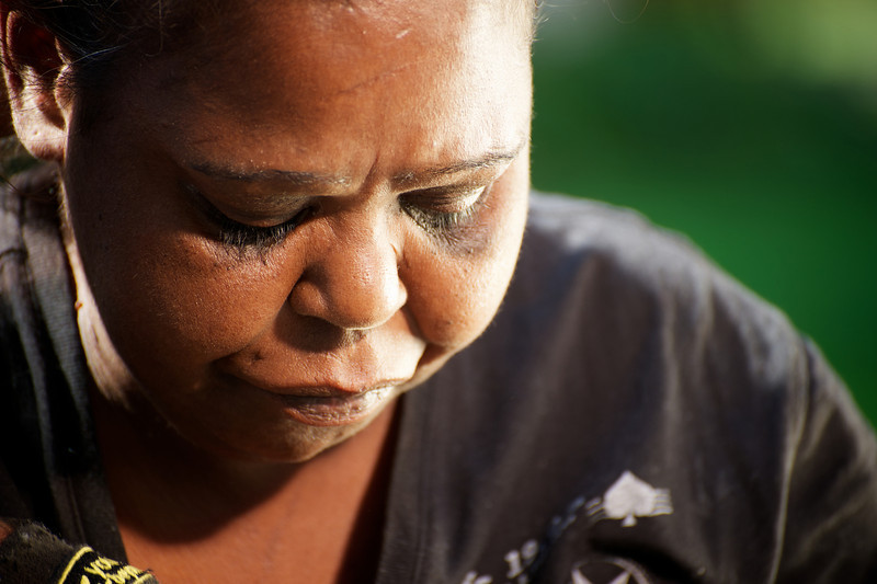 Indigenous Australian woman looking downwards, on a blurred green background