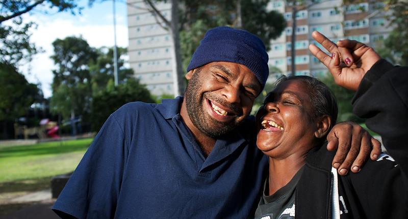 Indgienous Man and Woman Laughing in front of a High Rise