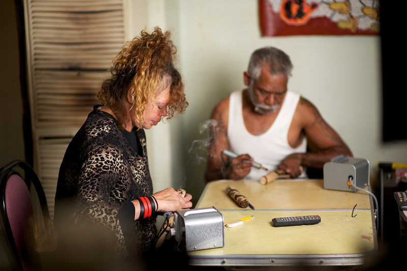 Aboriginal Australian Artists working on the crafting of Message Sticks using a soldering iron