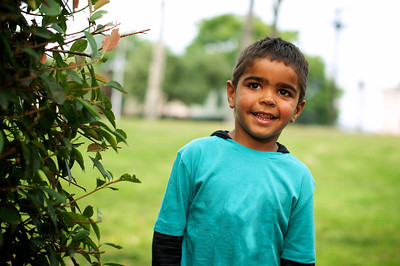 Little Aboriginal Boy next to a Bush