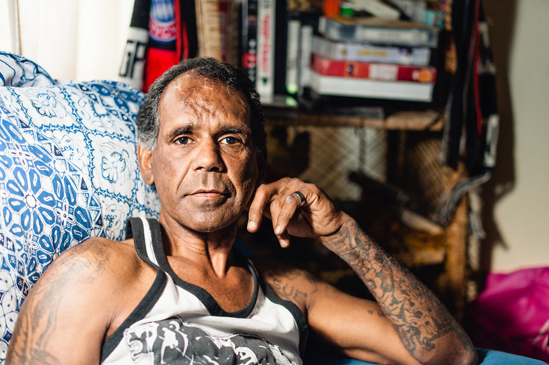 An Indigenous Australian Man seated Indoors