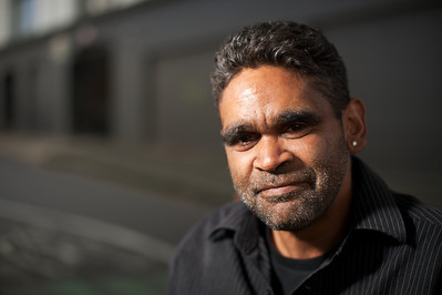 Young Indigenous Australian with an ear ring, outdoors and looking at camera