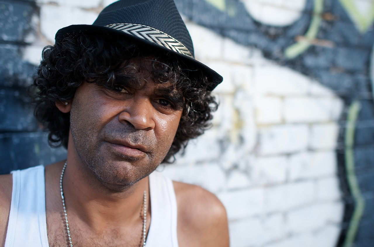 Indigenous Australian Man against Graffiti Brick Wall Background