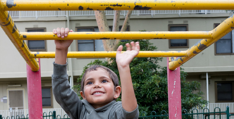 This photo shows a five-year-old Aboriginal boy in an urban setting in the Greater City of Melbourne, Australia.  The photo was made in the playground of a housing estate.  He is climbing on a piece of playground equipment.