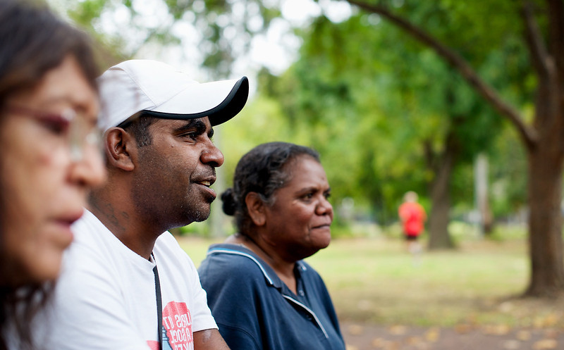 Three Aboriginal People seated outdoors