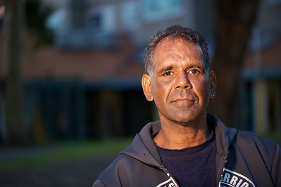 Upper body of a Indigenous Australian man photographed horizontally on a blurred background