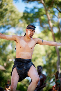 Aboriginal Dancer against background of eucalyptus trees and sky shot from below