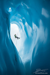 Man Rappelling past opening of blue ice cave on Matanuska Glacier, Alaska