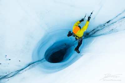 Ice flying from an ice ax swing while on lead out of a moulin on the Matanuska Glacier, Alaska
