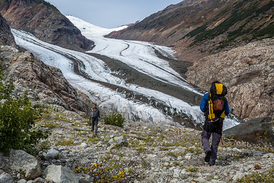 Backcountry hiking near large glacier in Canada. Man and woman walking a ridge above a glacier in the Boundary Range of British Columbia