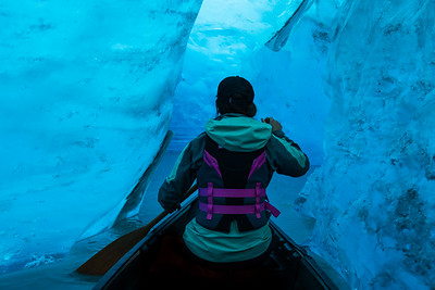 Woman paddling canoe into the ice cave of a glacier in Alaska