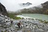 Hiker descending toward green glacial lake in Hatcher Pass area of Alaska