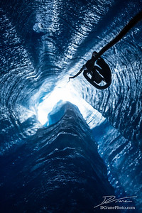 Looking up from inside a glacier with rope and ascender to climb out