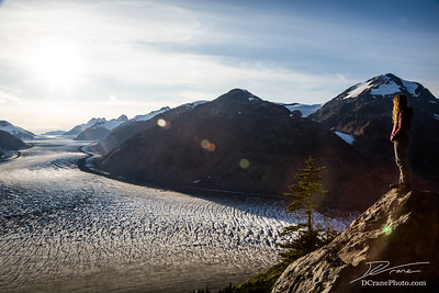 Sun flare over the Salmon Glacier as young blonde woman looks out over the scene