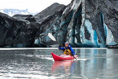 Kayaker paddling away from dark, moraine covered glacier in Alaska