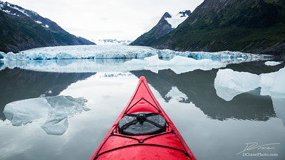 Red kayak floating among icebergs looking toward a glacier in Alaska.