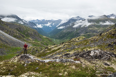 Hiker standing above glacial valley in Talkeetna Mountains, Alaska