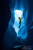 Ice climber viewed through a tunnel in the bottom of a moulin on the Matanuska Glacier in Alaska