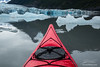 Kayak moving through icebergs in alpine lake of Alaska