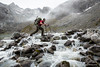 Hiker with large pack crossing a rocky river